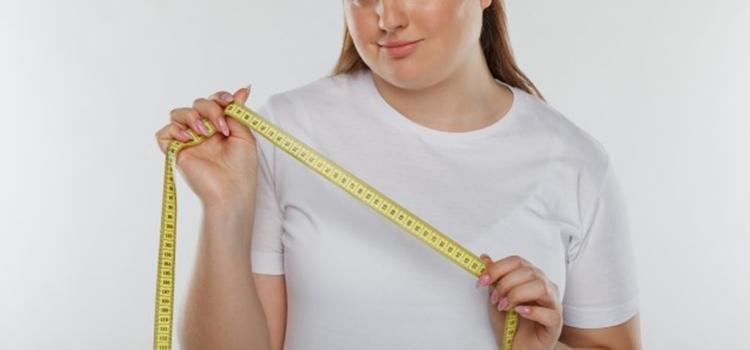 全身痩せの準備として胴囲を測ろうとする女性
