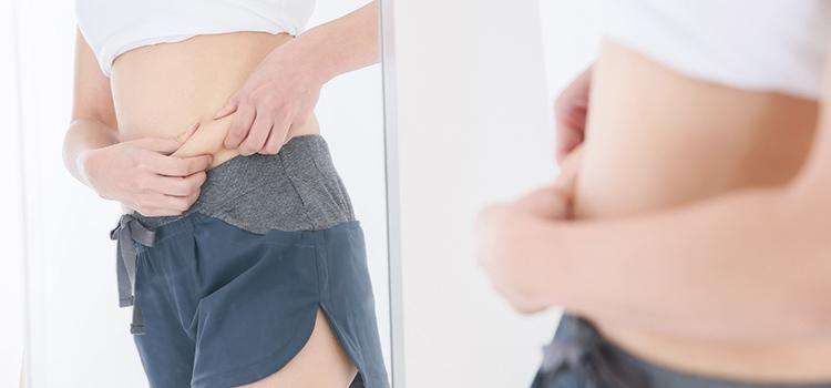 鏡でお腹の脂肪を確認する女性