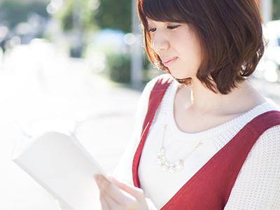 屋外で本を読む女性