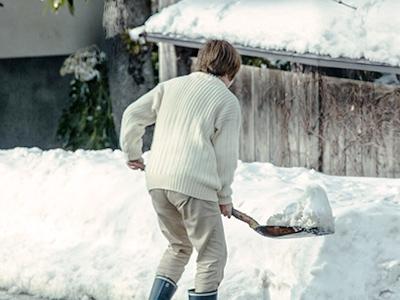 雪かきをする高齢女性