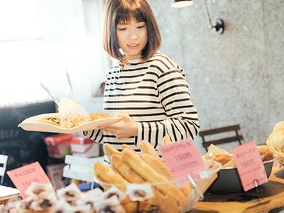 パン屋さんでどのパンを買おうか迷っている女性