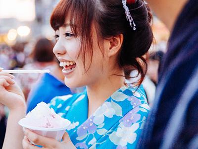 お祭りでかき氷を食べる女性