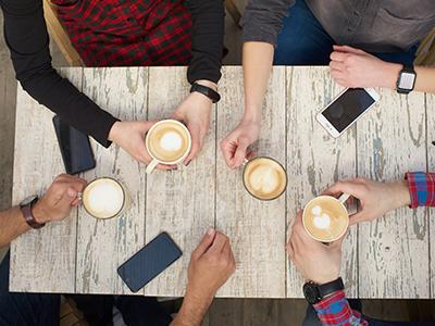 屋外のカフェでラテを飲むグループ