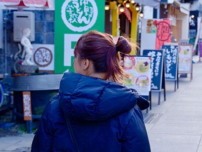 商店街で買い物をする女性