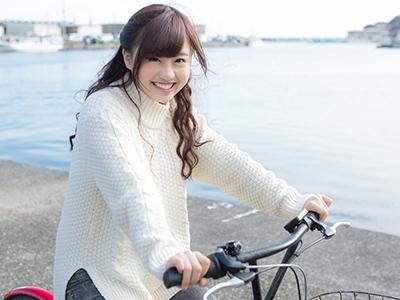 漁港でサイクリングをしている女性