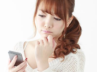 スマートフォンで口コミ情報を閲覧する女性