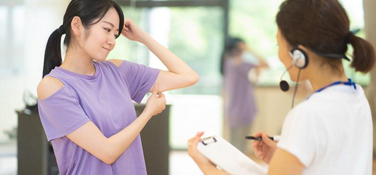 パーソナルジムでトレーナーに指導を受ける女性